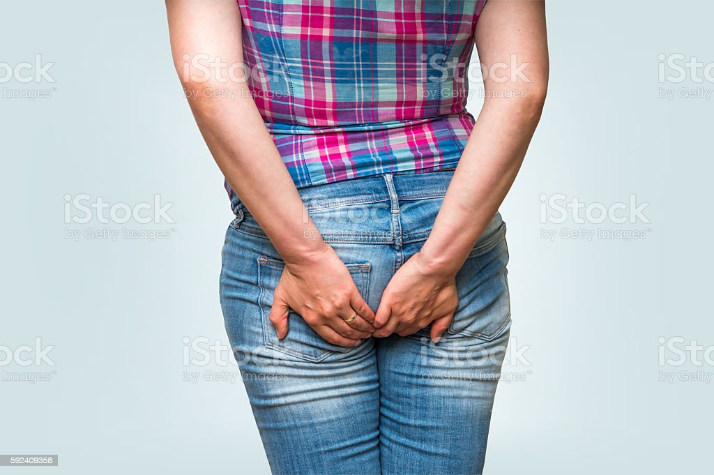 Woman holding her butt isolated on blue background stock photo