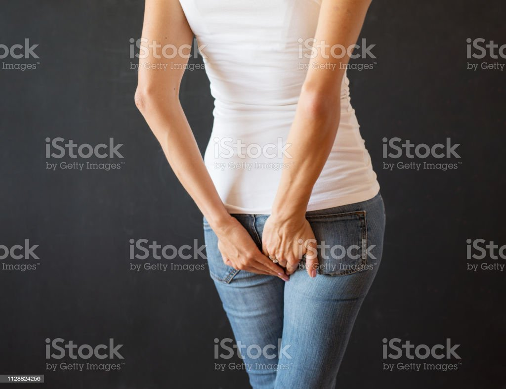 Woman holding her butt with hands stock photo