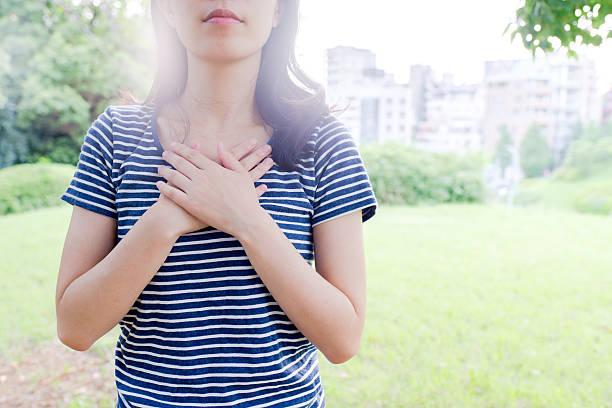 woman holding her chest - zukunftswünsche stock-fotos und bilder
