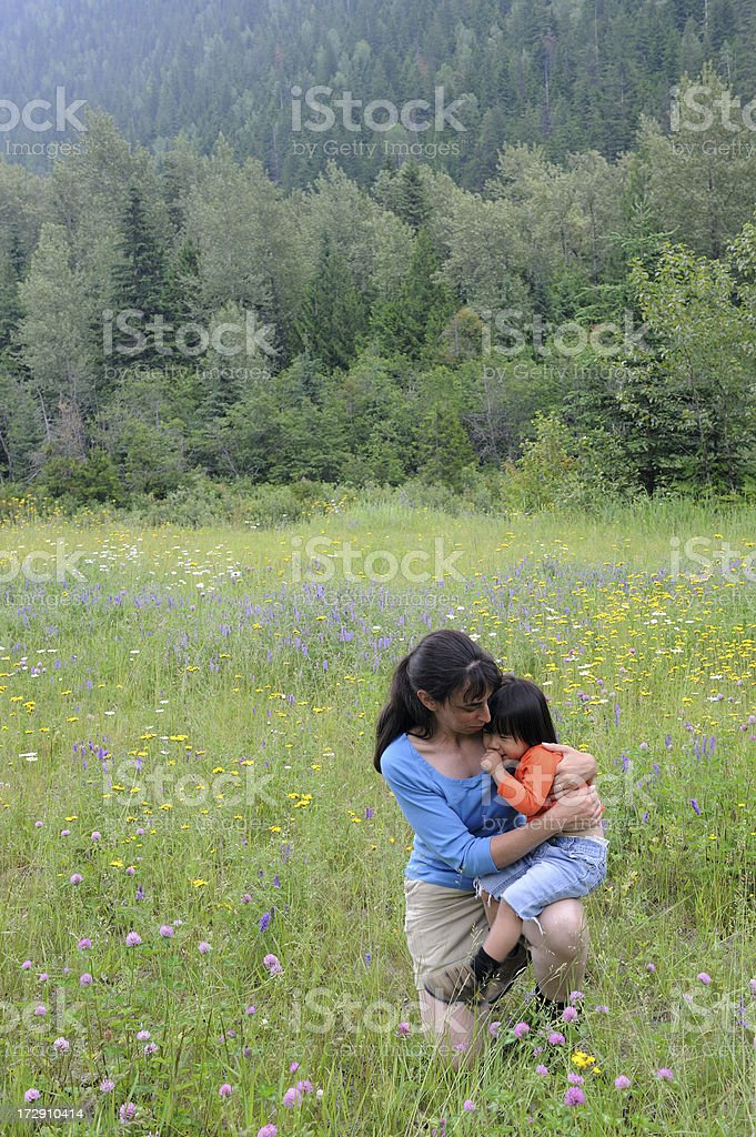 Woman Holding Her Daughter in a Flower Filled Meadow royalty-free stock photo