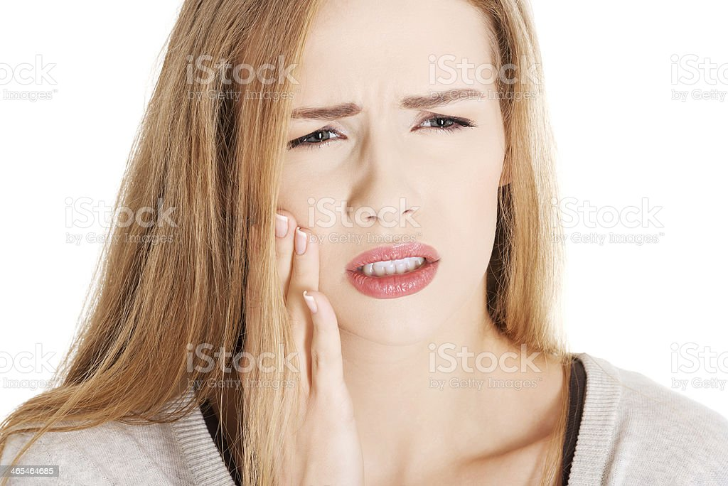 Woman holding her face due to toothache stock photo