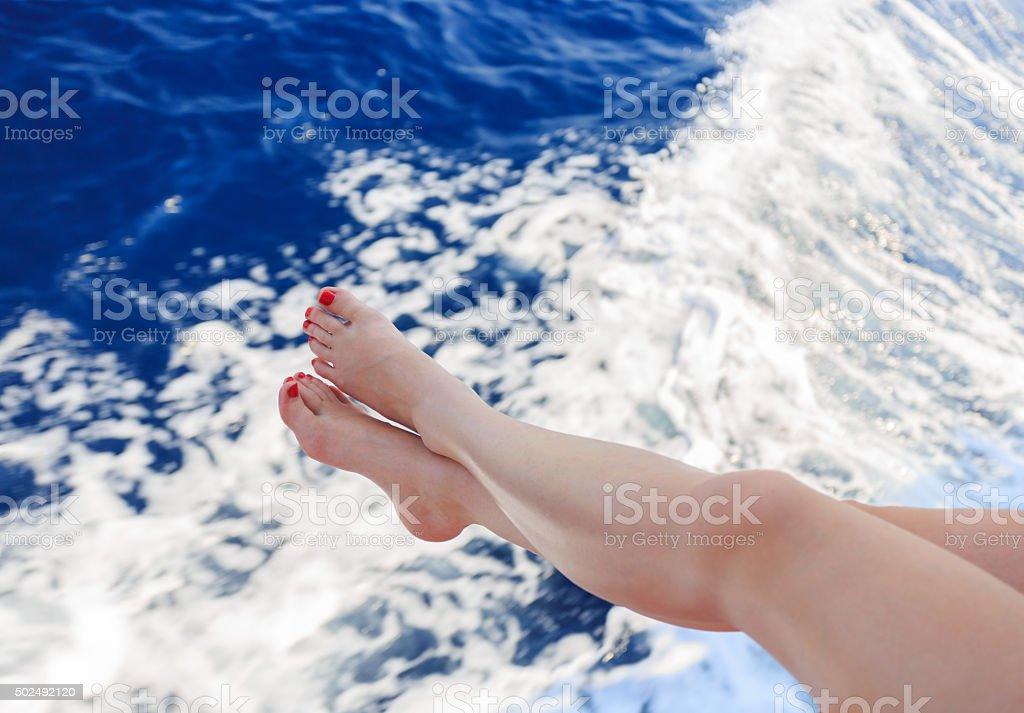 Frau hält Ihre Füße über dem Meer – Foto