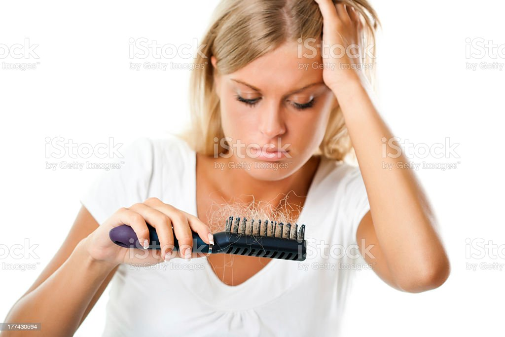 A woman holding her hair while checking her hair brush stock photo
