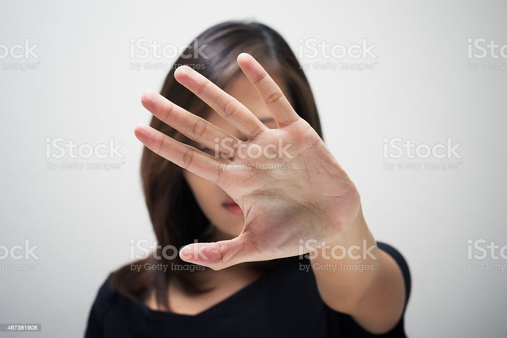A woman holding her hand straight out in front of her face stock photo
