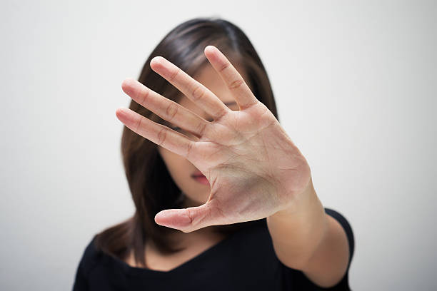 A woman holding her hand straight out in front of her face Young woman showing her denial with NO on her hand stop single word stock pictures, royalty-free photos & images