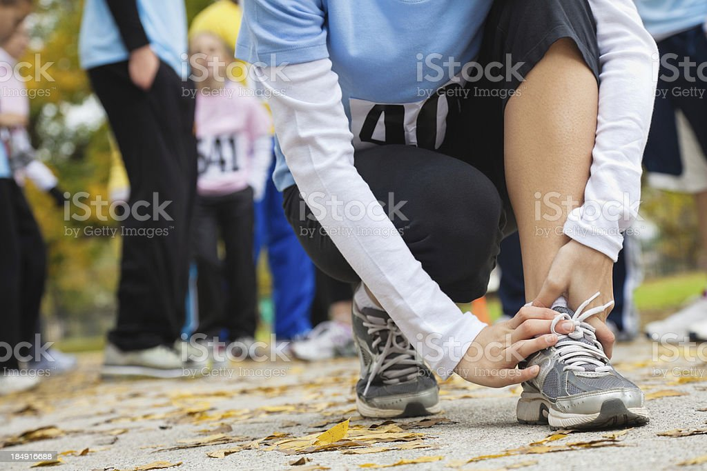 Woman holding her hurt ankle at a race stock photo