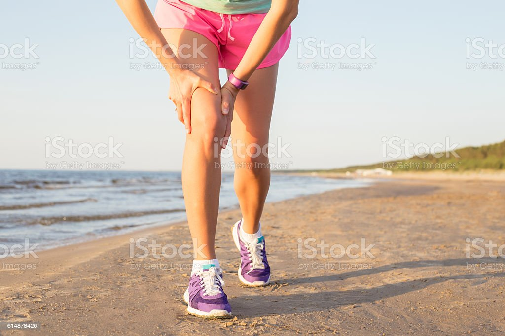 Woman holding her hurting knee stock photo
