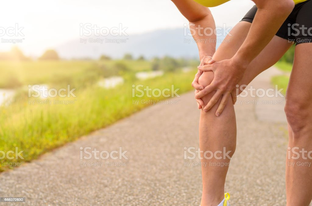 Woman Holding her Injured Knee stock photo