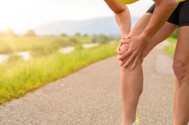frau hält ihr verletztes knie - orthopädisches hilfsmittel stock-fotos und bilder