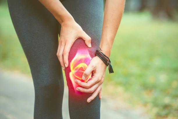 kvinna som håller i knäet med röd smärta. idrotts skötsel - knäskål bildbanksfoton och bilder