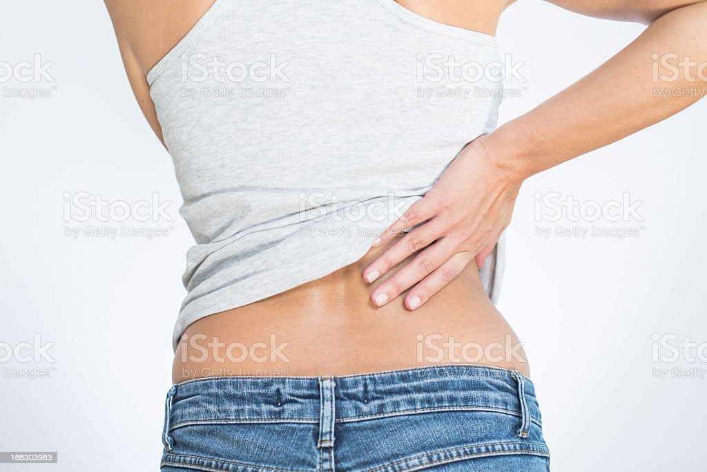 A woman holding her lower back signifying back pain stock photo