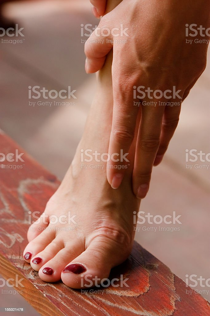 Woman holding her naked foot royalty-free stock photo