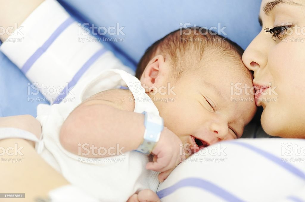 Woman holding her newborn baby at hospital stock photo