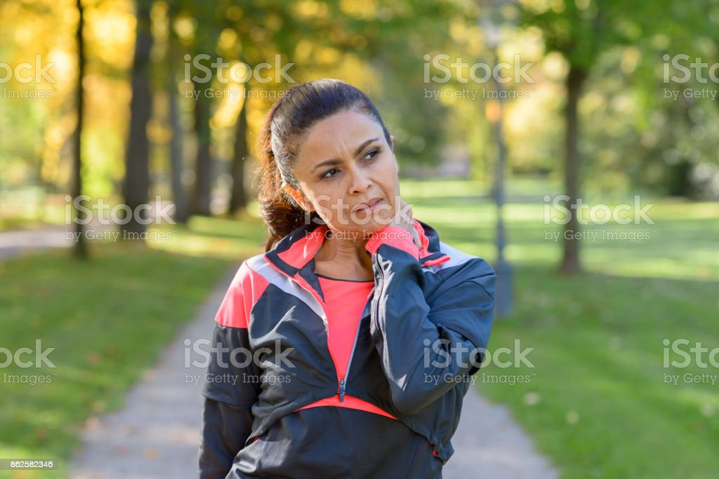 Woman holding her painful neck in park stock photo