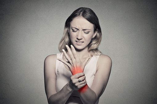 istock woman holding her painful wrist 484868646