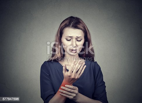 668285874 istock photo woman holding her painful wrist 577947598