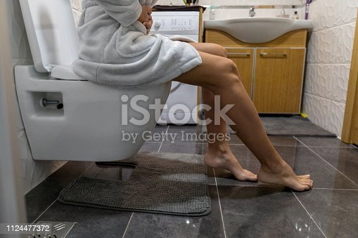 Woman holding her stomach in toilet