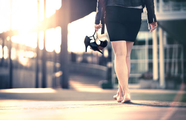 Woman holding high heels in hand and walking home from party barefoot. Businesswoman took off uncomfortable shoes. Lady with stilettos and miniskirt at sunrise or sunset in city street. stock photo