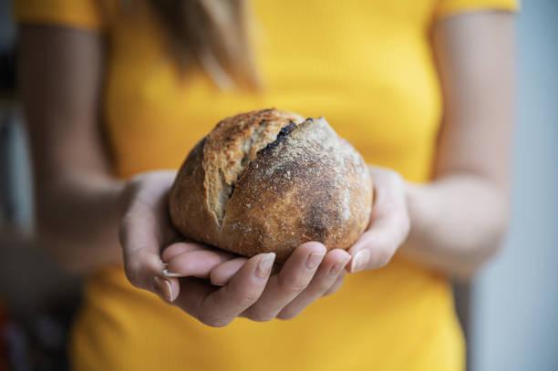 Woman holding home made bread bun stock photo