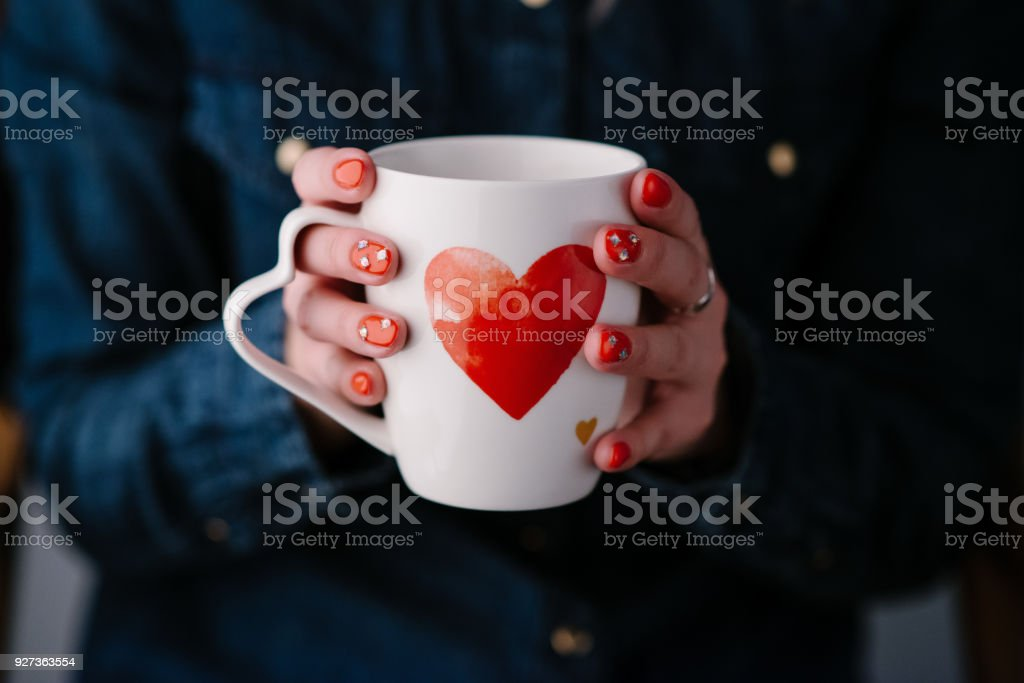 Woman holding hot cup of coffee with heart Woman holding  cup  with heart shape. Close up Adult Stock Photo