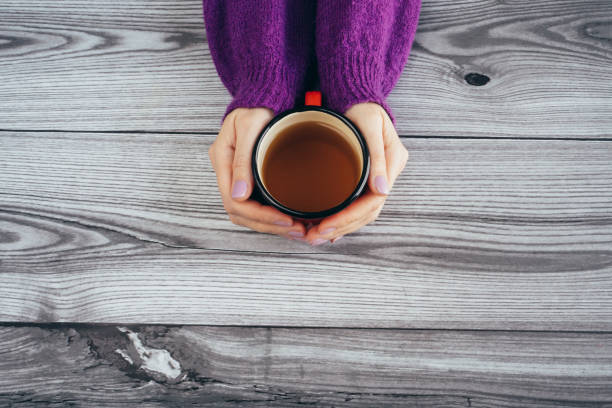 Woman holding hot cup of tea stock photo