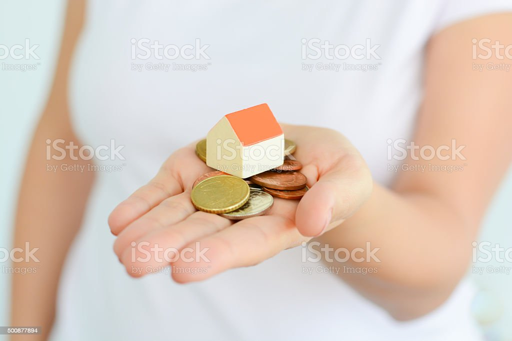 Woman holding house and money suggesting rising cost of houses stock photo