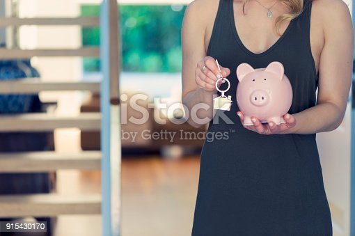 1048402108istockphoto Woman holding house keys and a piggy bank 915430170