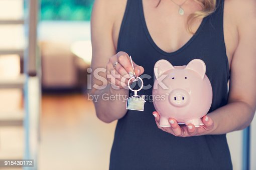 1048402108istockphoto Woman holding house keys and a piggy bank 915430172