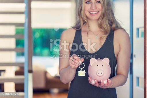 1048402108istockphoto Woman holding house keys and a piggy bank. 915430178
