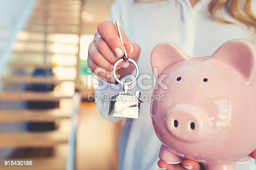 1048402108istockphoto Woman holding house keys and a piggy bank 915430186