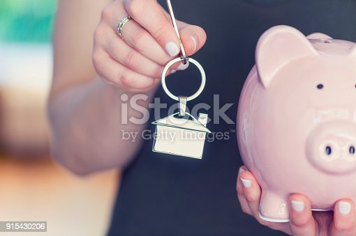 1048402108istockphoto Woman holding house keys and a piggy bank. 915430206