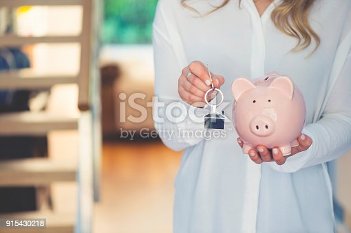 1048402108istockphoto Woman holding house keys and a piggy bank 915430218