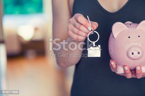 1048402108istockphoto Woman holding house keys and a piggy bank. 916277600