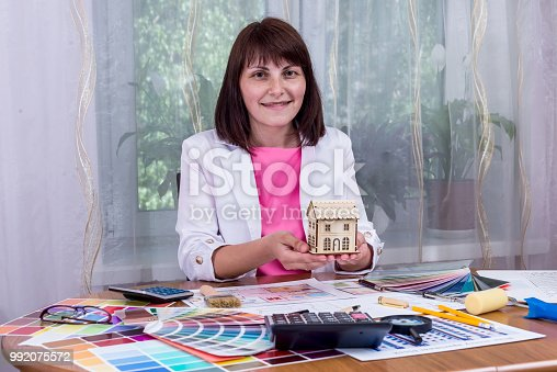 istock Woman holding house model in palms over drawings 992075572