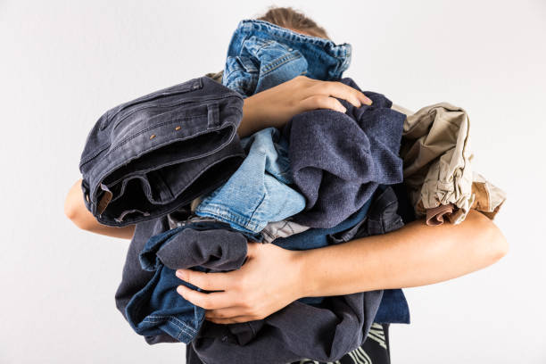 Woman holding huge pile of clothes - laundry concept stock photo