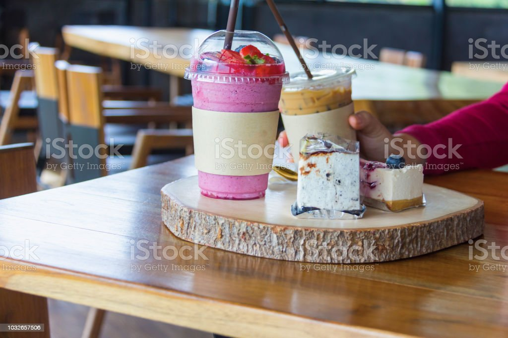 woman holding iced blueberry plastic cup in cafe stock photo