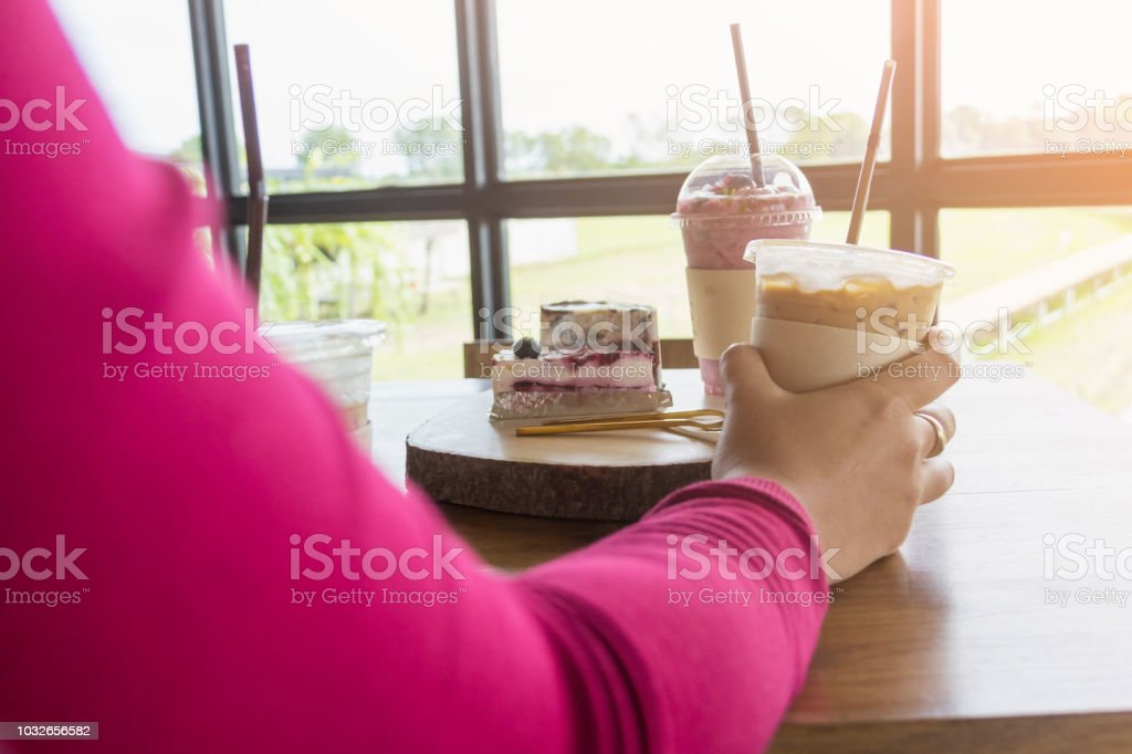 woman holding iced blueberry plastic cup in cafe with warm light stock photo