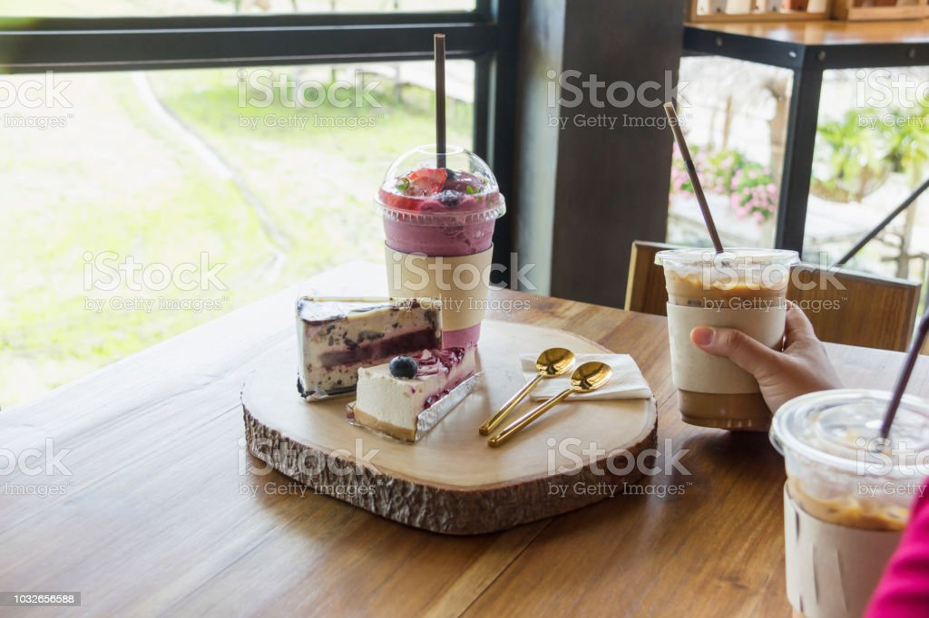 woman holding iced coffee plastic cup in cafe stock photo