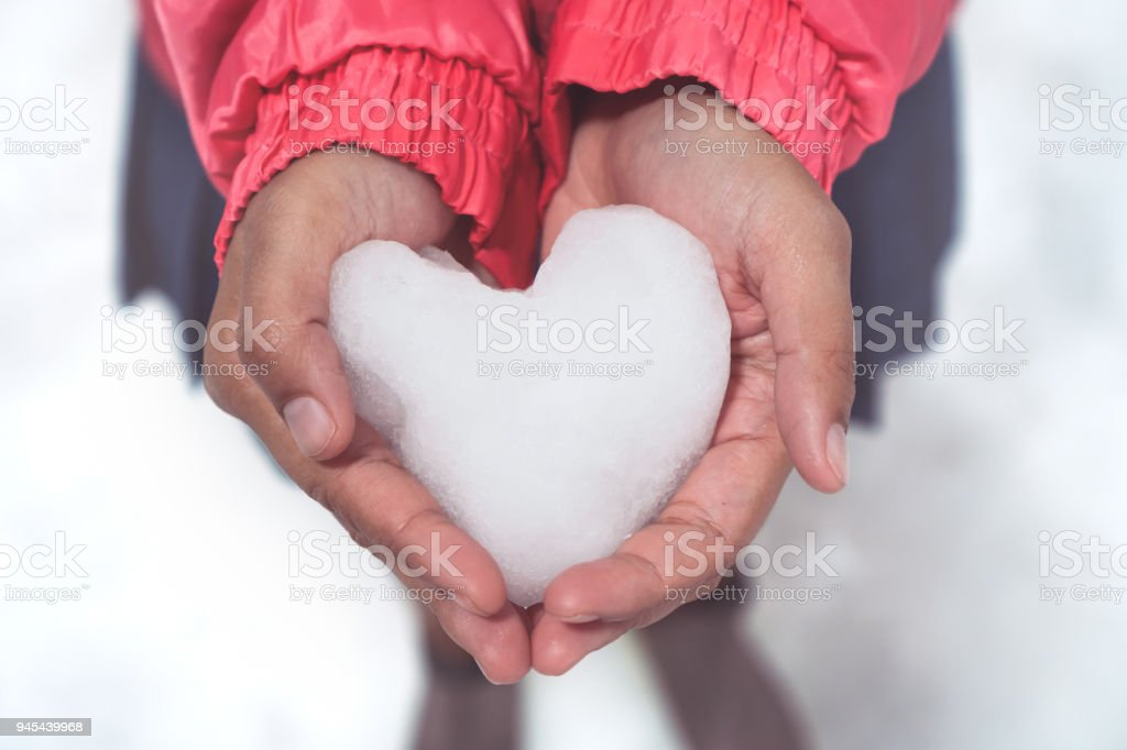 Woman holding icy snow heart in hands stock photo