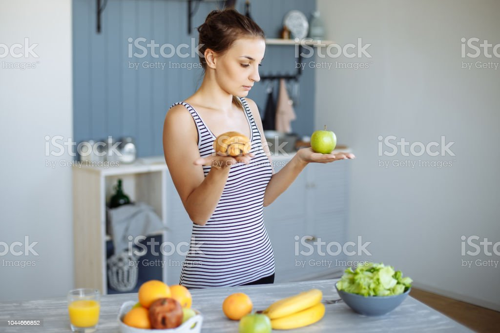 Woman holding in hand cake sweet bun and apple fruit choosing, trying to resist temptation, making the right dietary choice. stock photo