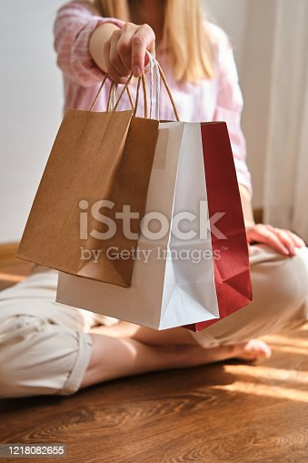 Woman holding in hand shopping package. Paper bag. Sale in store. Beautiful young girl after shopping in fashion shop. Customer buy present online. Black friday sale. Holiday special offer, discount