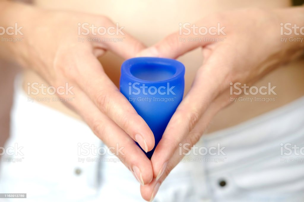 Woman holding in hands blue menstrual cup near bare belly. Feminine...