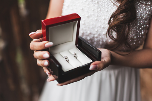 Woman holding in hands box with pearl earrings. Getting ready of bride on wedding