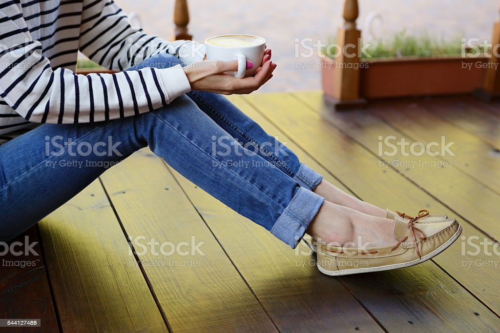 Woman holding in hands cup of coffee sitting on floor stock photo