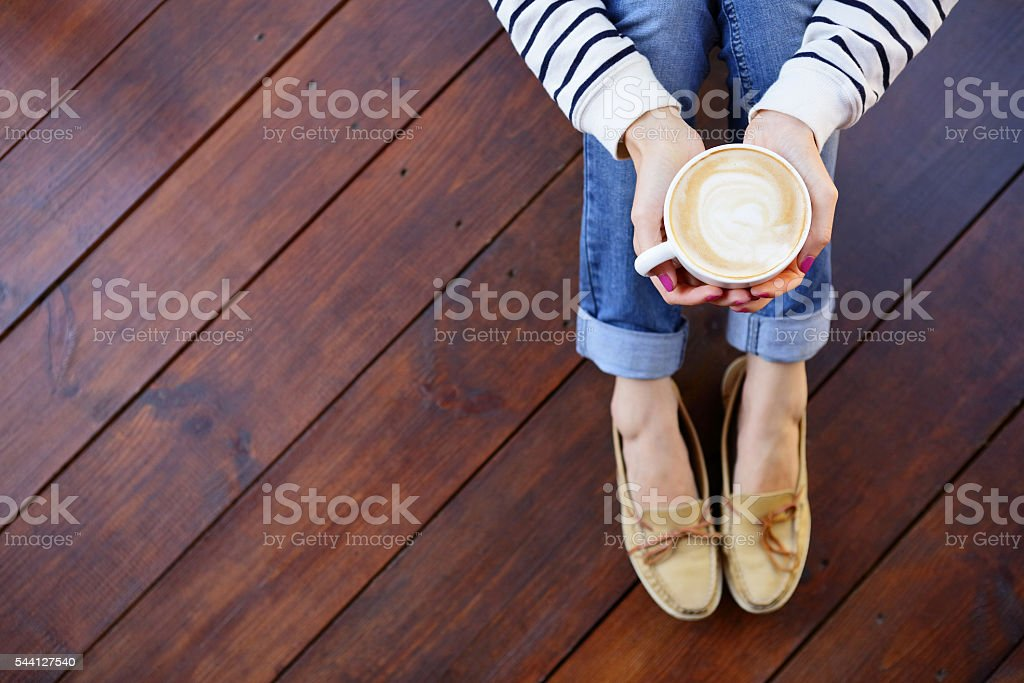 Woman holding in hands cup of coffee sitting on floor