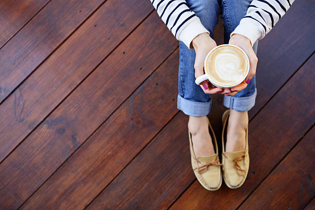 woman holding in hands cup of coffee sitting on floor - hartholz stock-fotos und bilder