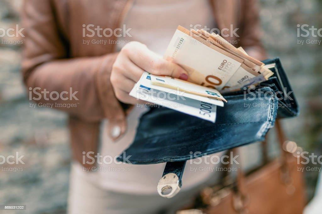 Mujer sosteniendo en cartera de las manos con dinero del euro. Chica de ciudad es sacar dinero de la cartera - foto de stock