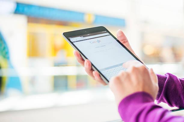 женщина держит для ipad mini - google стоковые фото и изображения