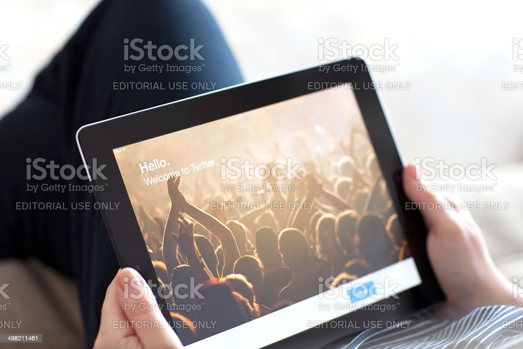 Woman holding iPad with App Twitter on the screen stock photo