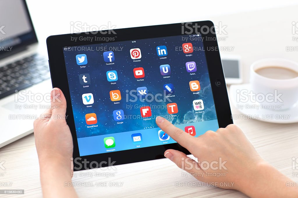 Woman holding iPad with social media app on the screen